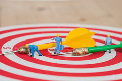 Miniature worker toy on red dart board Stock Photography
