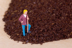 Miniature worker working on grinded coffee Royalty Free Stock Images