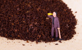 Miniature worker working on grinded coffee Royalty Free Stock Photo