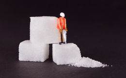 Miniature worker working on a sugar cube Stock Photo