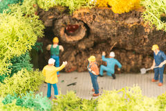 Miniature workers clearing a pathway after storm Stock Photos