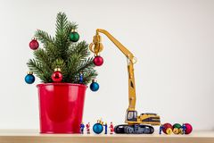 Miniature workers decorating christmas tree royalty free stock image