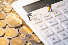 Miniature workers digging tax button on calculator on pile of coins stock photos