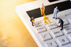 Miniature workers digging tax button on calculator stock photo