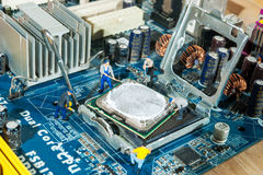 Miniature workers installation CPU. Computer motherboard Stock Photo