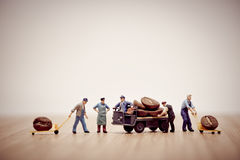 Miniature workers loading coffee beans on truck Royalty Free Stock Photography