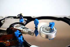 Miniature workers repair hard disk drive Royalty Free Stock Photography