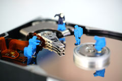 Miniature workers repair hard disk drive Royalty Free Stock Photos