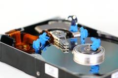 Miniature workers repair hard disk drive Royalty Free Stock Images