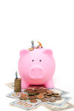 Miniature workers save coins in piggy bank Royalty Free Stock Images