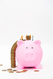 Miniature workers save coins in piggy bank Royalty Free Stock Photos