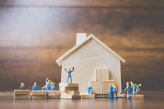 Miniature workers team build a wooden house. With wooden background royalty free stock photos