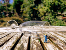 Miniature workman collecting water or wine with jerrycan from fa. Llen champagne glass outside on wooden table. Leisure concept Royalty Free Stock Photography