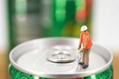 Miniature workman open a can. Miniature workman on top of soda can with blurred background. Business concept Stock Images