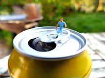 Miniature workman sitting on top of soda can. With blurred background. Business concept Royalty Free Stock Images