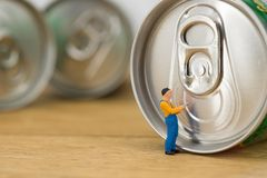Miniature workman open a can. Miniature workman on top of soda can with blurred background. Business concept Royalty Free Stock Photo
