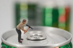 Miniature workman open a can. Miniature workman on top of soda can with blurred background. Business concept Stock Image