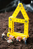 Miniature workmen building a house. Tiny miniature workmen with their equipment building a house on a rough earth building site Royalty Free Stock Images