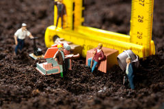 Miniature workmen building a house Stock Photos
