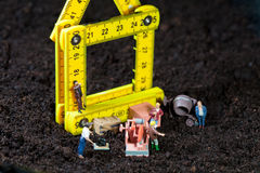 Miniature workmen building a house. Tiny miniature workmen with their equipment building a house on a rough earth building site Stock Image