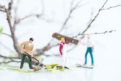 Miniature workmen busy in felling and cutting trees close up Royalty Free Stock Images