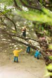Miniature workmen clearing fallen trees Royalty Free Stock Images