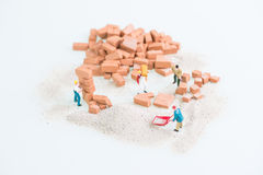 Miniature workmen doing construction brickwork top view close up Stock Photos