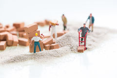 Miniature workmen doing construction work with bricks and sand background Royalty Free Stock Photo