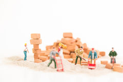 Miniature workmen working together in laying brickwork close up Stock Image