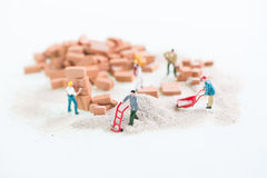 Miniature workmen working together in laying brickwork top view close up Stock Images