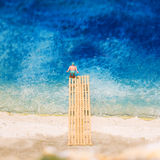 Miniature world: fat man jumping into water taking a holiday at the beach. Summer lifestyle, vacation and tourism concept. Stock Photos