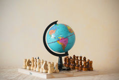 Miniature world globe model standing on chess wooden board Stock Images