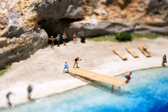 Miniature world: people in different situations taking a holiday at the beach. Summer lifestyle, vacation and tourism concept. Stock Image