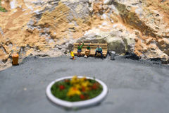 Miniature world: people waiting for their transport on the bus stop. Tourism and public transport theme. Stock Images