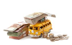 Saving for travel. Miniature  yellow bus carry money isolated on white background