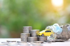Miniature yellow car model on stack of coins money in glass bottle on nature green background, Saving money for car, Finance and stock photography