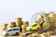 Miniature yellow car model on stack of coins money in glass bottle on wtite background, Saving money for car, Finance and car loan. Investment and business royalty free stock photo