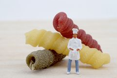 Miniaturen des Chefs mit Teigwaren Stockfoto