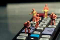 Miniaturen van arbeiders die een afstandsbediening bevestigen Stock Foto