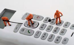 Miniaturen von den Arbeitskräften, die ein schnurloses Telefon reparieren Lizenzfreie Stockbilder