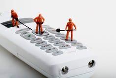 Miniaturen von den Arbeitskräften, die ein schnurloses Telefon reparieren Lizenzfreie Stockfotografie