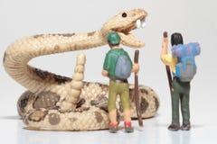 Miniaturen von Wanderern vor einer riesigen Klapperschlange Lizenzfreies Stockbild