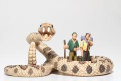 Miniaturen von Wanderern vor einer riesigen Klapperschlange Stockbilder
