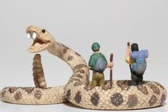 Miniaturen von Wanderern vor einer riesigen Klapperschlange Stockfotos