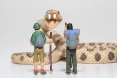Miniaturen von Wanderern vor einer riesigen Klapperschlange Lizenzfreie Stockfotografie