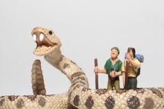 Miniaturen von Wanderern vor einer riesigen Klapperschlange Lizenzfreies Stockfoto