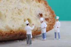 Miniatures of cooks with bread Royalty Free Stock Photography