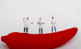 Miniatures of cooks and red hot chili pepper Royalty Free Stock Images