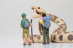 Miniatures of hikers in front of a giant rattlesnake Royalty Free Stock Image