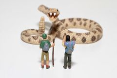 Miniatures of hikers in front of a giant rattlesnake Stock Photo